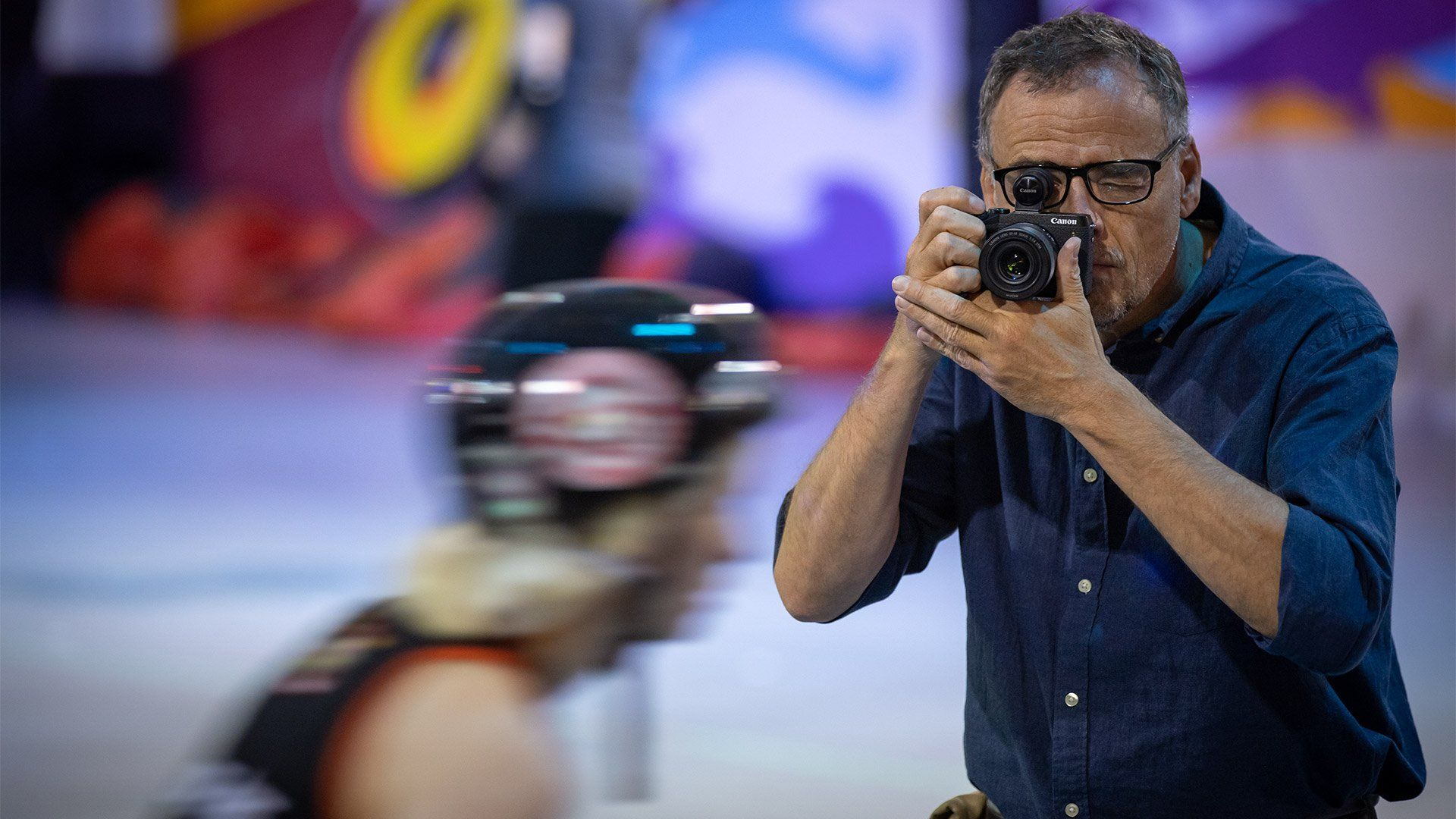 Photographer Piotr Malecki is in sharp focus as he photographs a fast-moving roller skater, who is blurred.